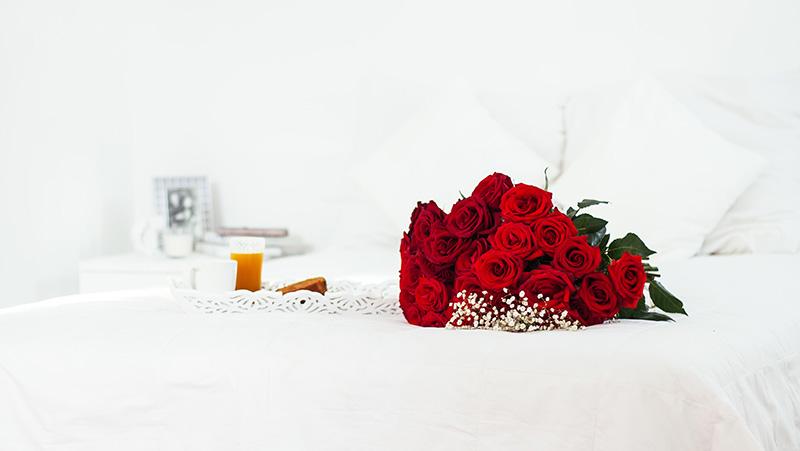 ホテルのベッドの上にサプライズで置かれた花束