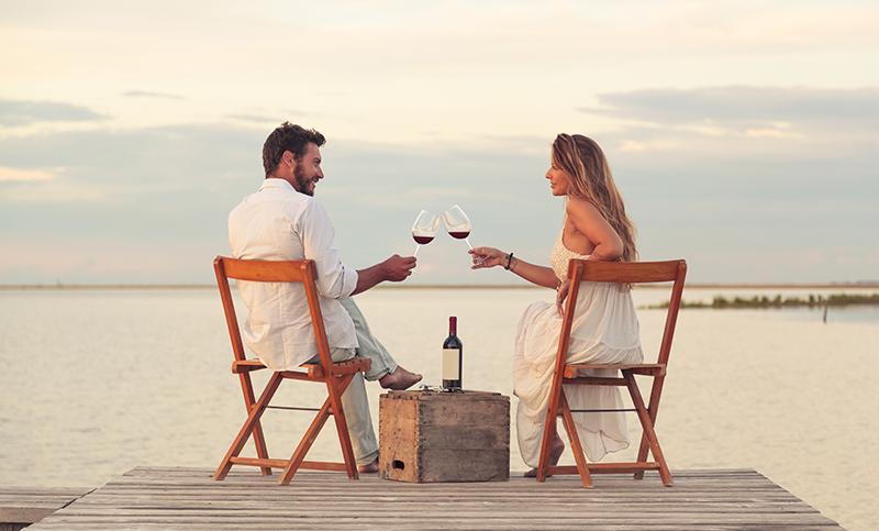 海の見える絶景スポットでヴィンテージワインを飲むカップル