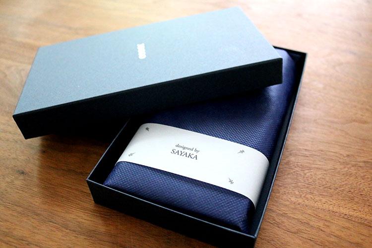 ボックスを開けるとデザイナーの名前が書かれた帯が