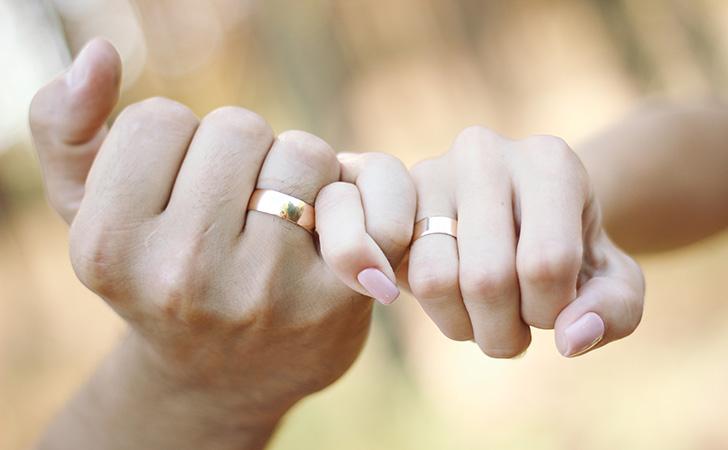 ペアリングを指にはめているカップル