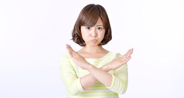 ダメ!のサインを見せる女性のイメージ