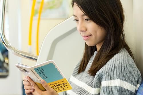 本のスマホケースでスマホを見てる女性