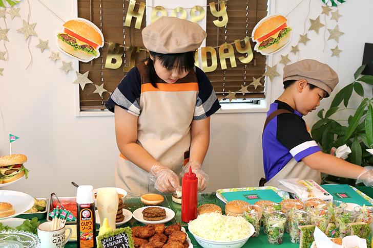 ハンバーグの上にチーズを乗せている バーガーショップ(モスバーガー風)をテーマにした子供の誕生日パーティー演出