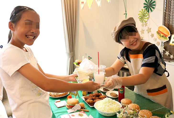 手渡す時にニッコリと笑顔を見せる バーガーショップ(モスバーガー風)をテーマにした子供の誕生日パーティー演出