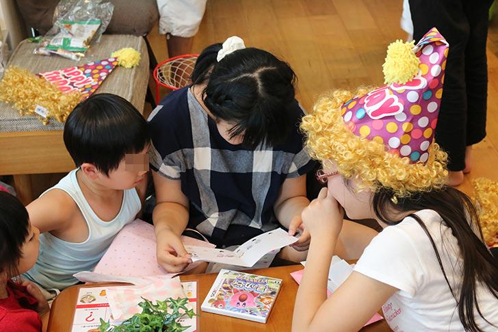 誕生日プレゼントのメッセージカードを見ている バーガーショップ(モスバーガー風)をテーマにした子供の誕生日パーティー演出