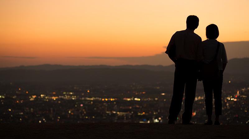 美しい夜景が見える丘の上など、旅先のロマンチックな場所でプレゼントを渡すサプライズ