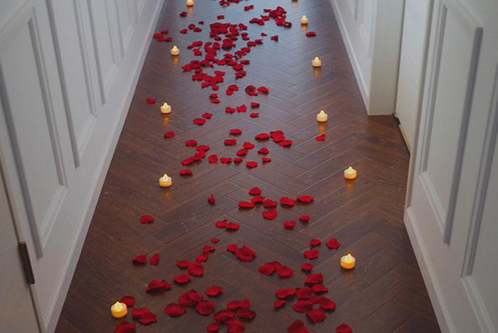 花びらとキャンドルが続く道の先にある50本の赤バラがあるプロポーズ