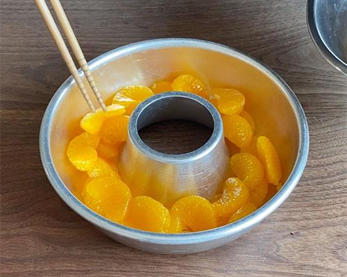 汁気を切ったみかんの缶詰を型に並べる。